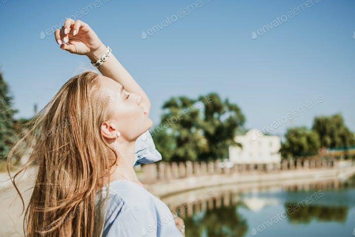 Sommer-Haarpflege, Sonnenschutz für Haare, Konditionierung. Blondes Mädchen mit langen Haaren steht in der Nähe von Fluss in