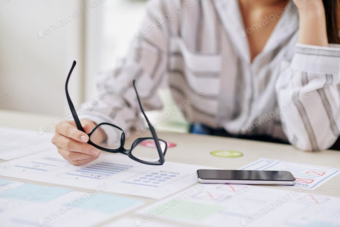 Crop businesswoman with eyeglasses and phone at desk