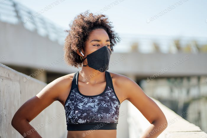 Afro athletic woman standing outdoors.