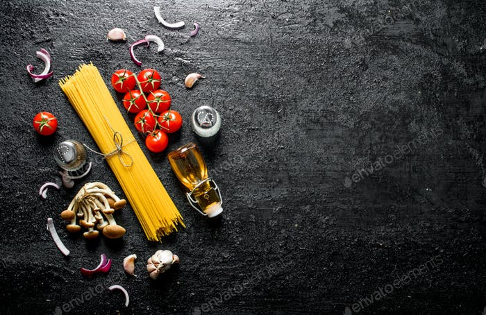 Raw spaghetti with onion slices, tomatoes, mushrooms and oil in a bottle.