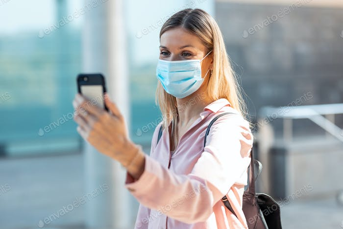 Beautiful blonde woman in face mask doing a selfie with smartphone in the street.