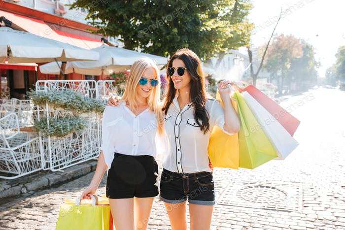 Two young women with shopping bags walking on the street