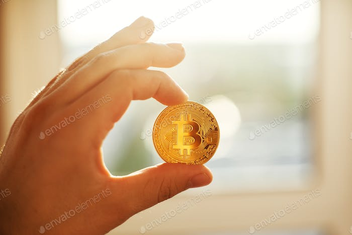 Hand holding shiny golden bitcoin in light, gold money