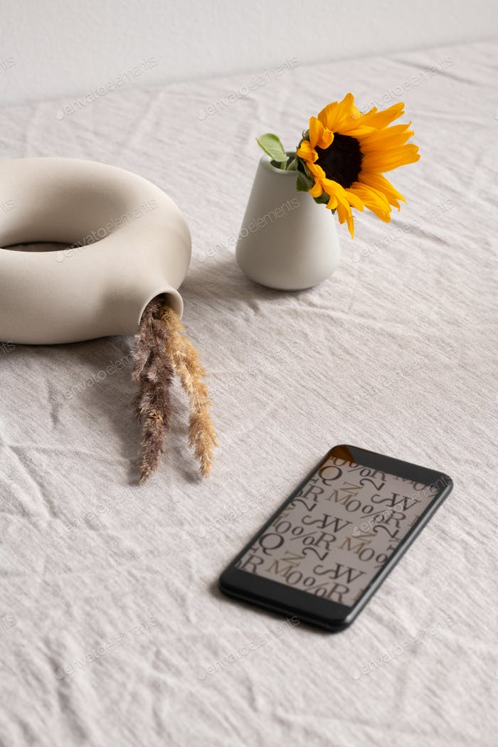 Smartphone, sunflower in ceramic glass and ringshaped vase with dried spikes