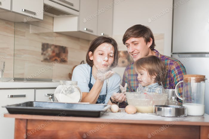 young parents and adorable little kid playing with floor on kitchen