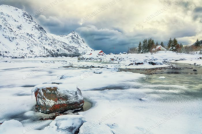 Dramatic winter scenery with snowy  mountain peaks  on the shore