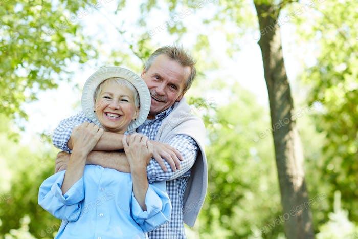 Seniorenpaar umarmen in Park