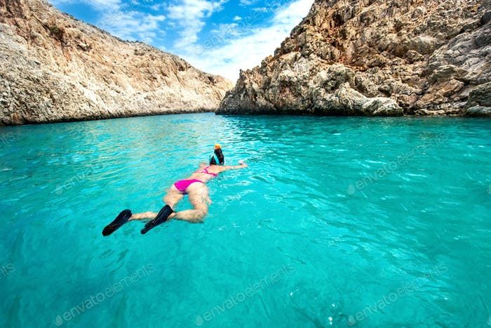 Traveling and watersports details - wide angle view of woman enjoying swimming and snorkeling