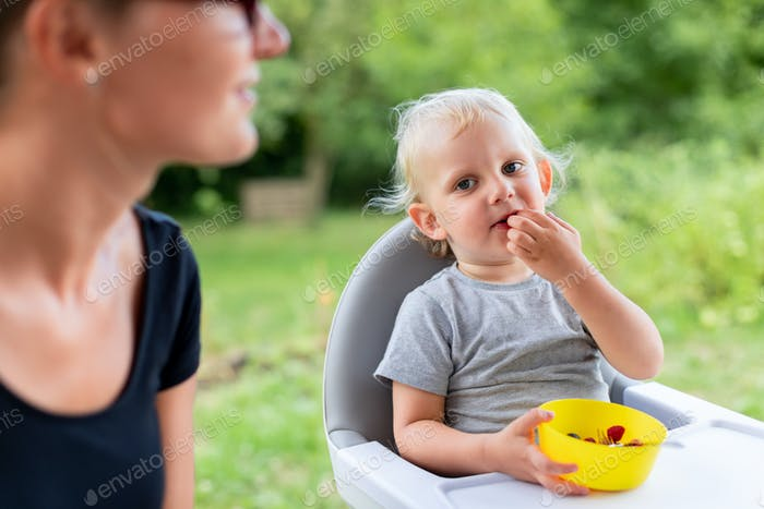 Baby eating with his mom outdoor