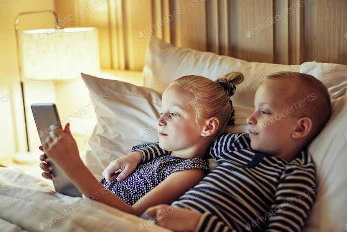 Cute little brother and sister lying in bed watching videos