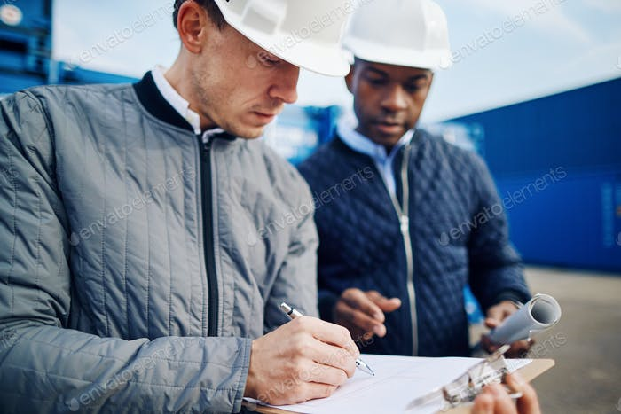 Two engineers standing in a shipping yard discussing an inventory