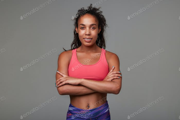 Positive young slim curly brunette woman with dark skin folding hands on her chest while smiling