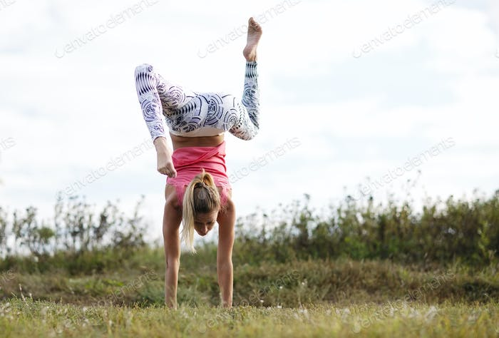 Agile young woman doing a handstand