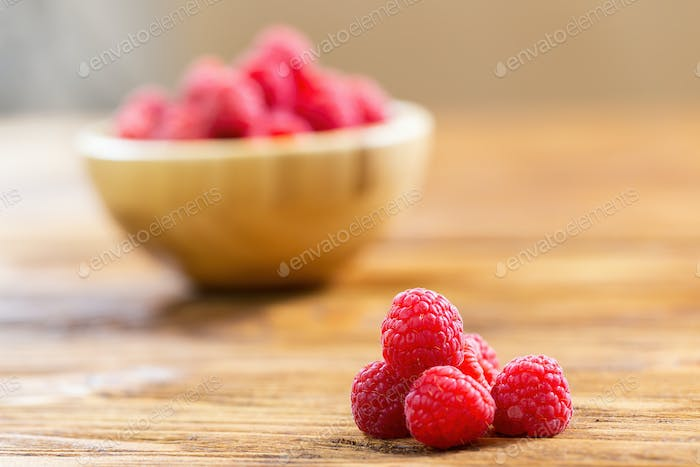 Raspberries lying on wooden table in front of brown bowl