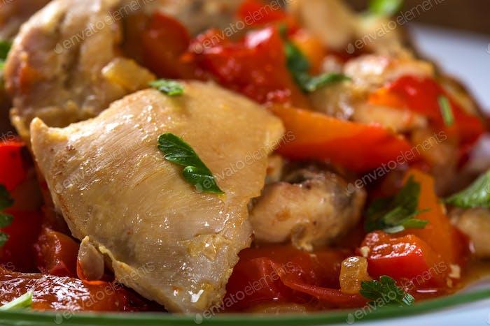 Teller mit Hühnereintopf mit rotem Pfeffer und Kräutern