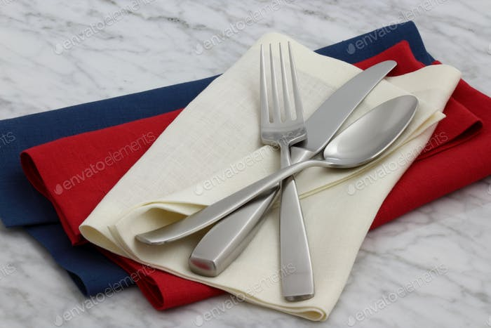 silverware and hemstitch napkin on antique carrara marble