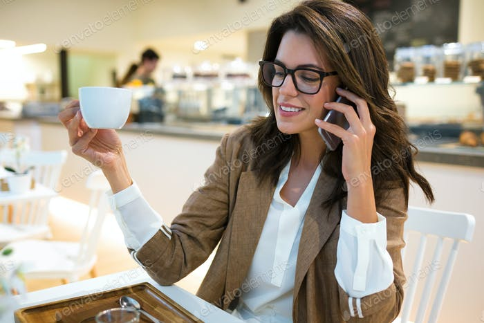 Smiling young businesswoman talking with her mobile phone in the coffee shop.