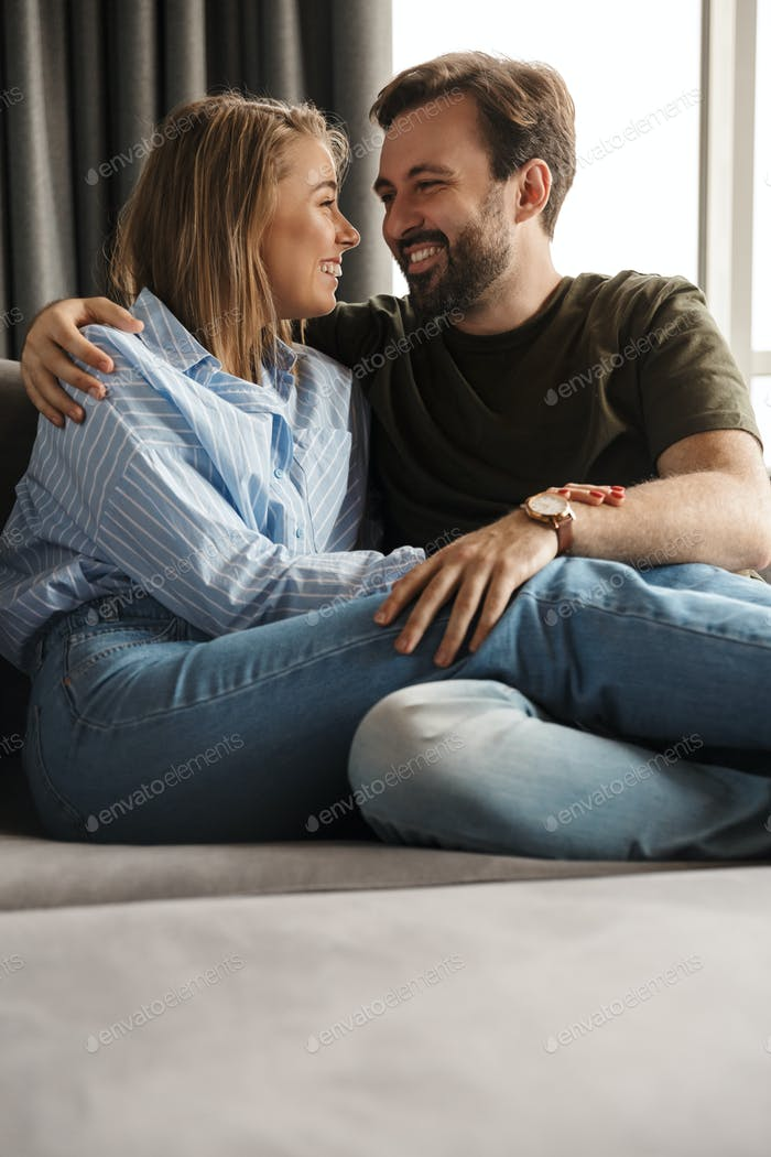 Photo of cheerful couple smiling and hugging while sitting on sofa