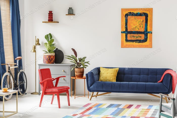 Red chair and royal blue lounge placed in bright sitting room in