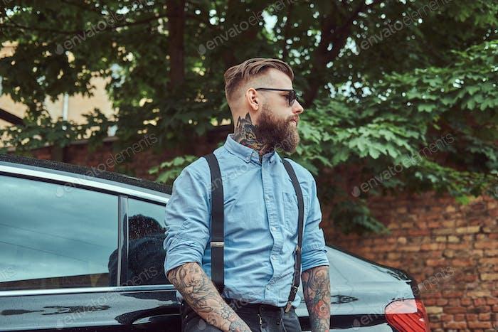 Altmodischer tätowierter Hipster-Typ in einem Hemd mit Hosenträgern, stehend in der Nähe von schwarzem Auto im Freien.