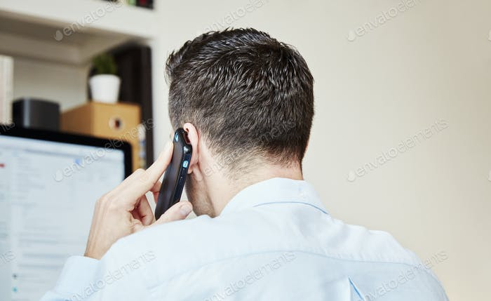 A man making a phone call and looking at his computer screen.
