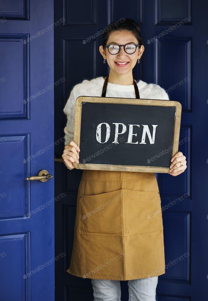 Ein fröhlicher Kleinunternehmer mit offenem Schild