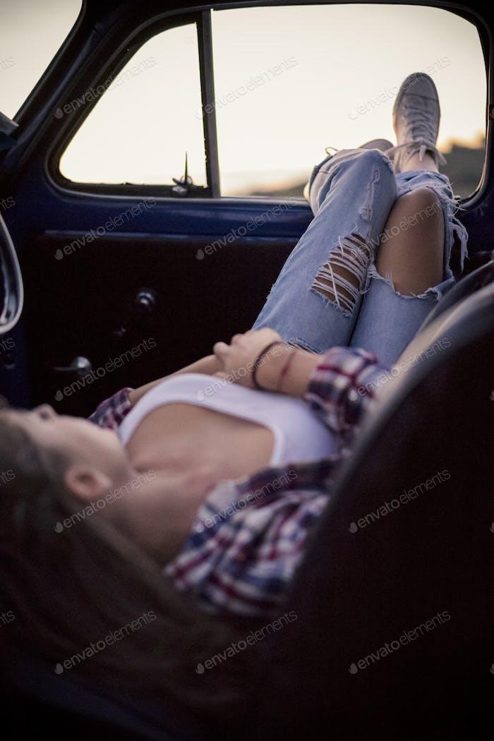 Junge Frau entspannt in einem Oldtimer
