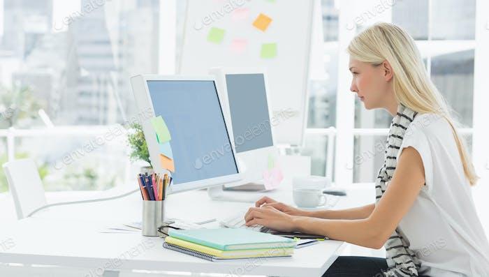 Seitenansicht einer lässigen jungen Frau mit Computer in einem hellen Büro