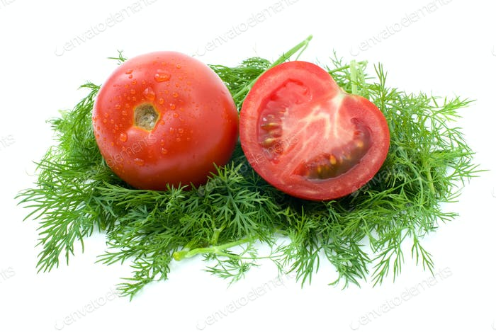 Whole and half of tomato over some dill