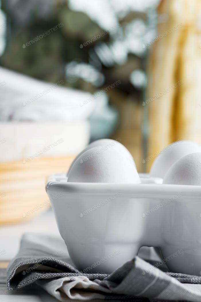 Keramikbehälter mit natürlichen Bio-Bauerneiern auf einem verschwommenen Küchenhintergrund