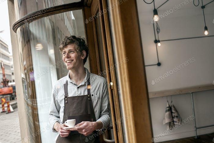 Lächelnde männliche Barista halten Kaffeetasse außerhalb shop