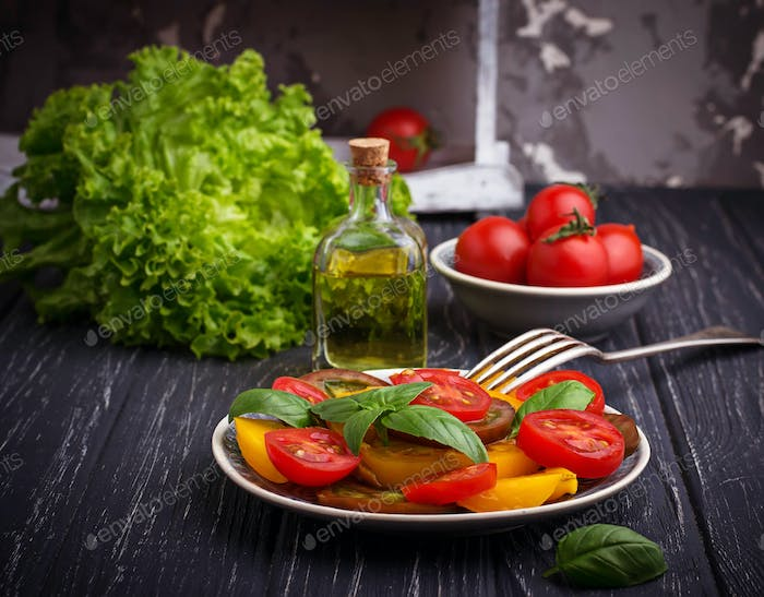 Colorful tomatoes salad in black background