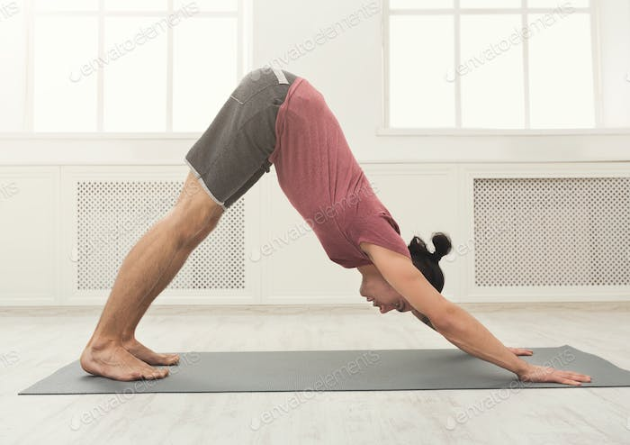 Yoga stretching. Young man in dog pose