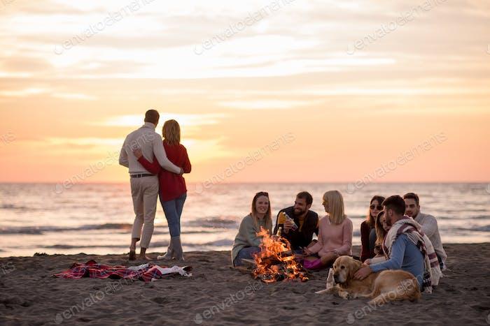 Paar genießen mit Freunden bei Sonnenuntergang am Strand