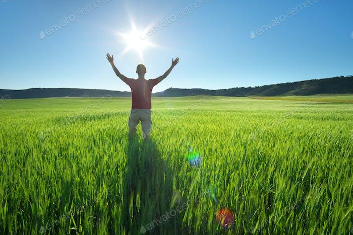 Mann auf grüner Wiese und Sonnenschein.