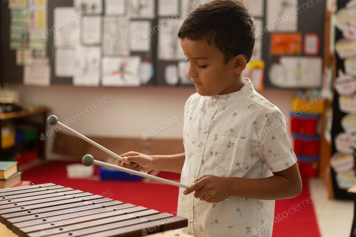 Side view of cute mixed-race schoolboy playing xylophone in a classroom at elementary school