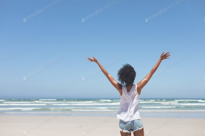 Happy young woman standing with open arm at beach on a sunny day