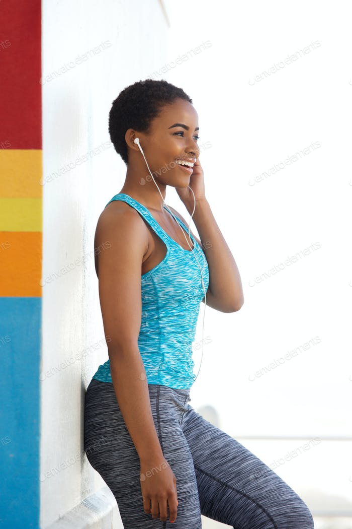 fit young black woman listening to music with earphones