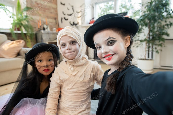 Happy halloween girl making selfie with two kids in costumes