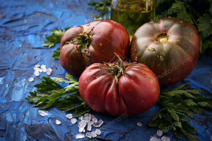 Tomato, salt and parsley on blue concrete background
