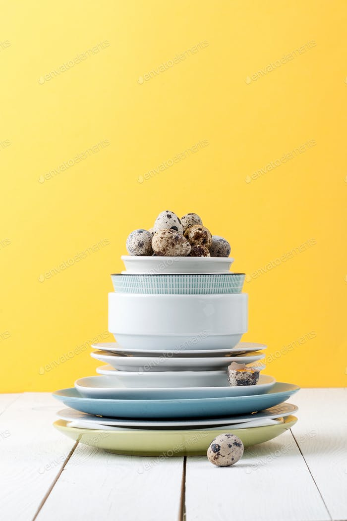 A stack of different tableware and quail eggs on a white wooden