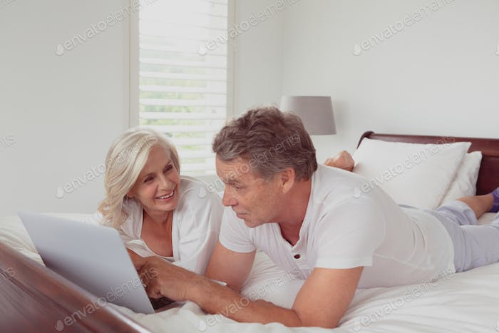 Active senior Caucasian couple using laptop while lying on bed in bedroom at comfortable home