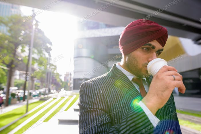 Indian businessman with turban outdoors in city drinking coffee