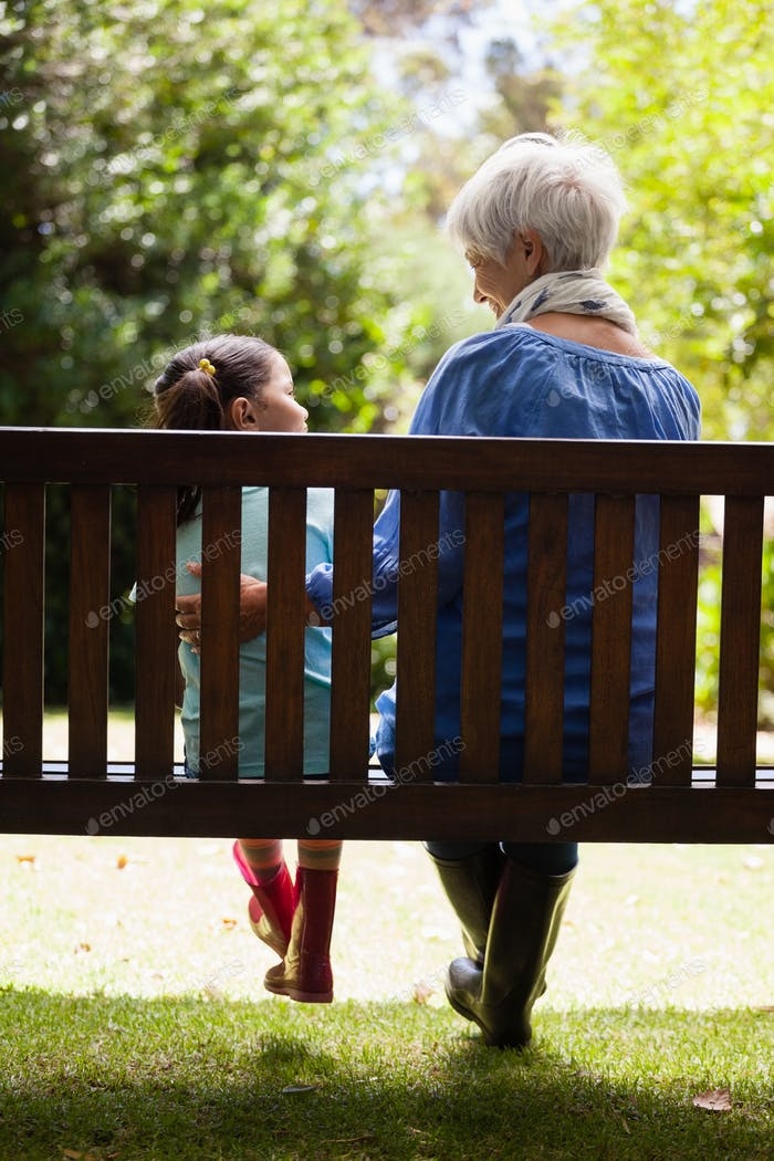Rear view of grandmother and granddaughter sitting on wooden bench