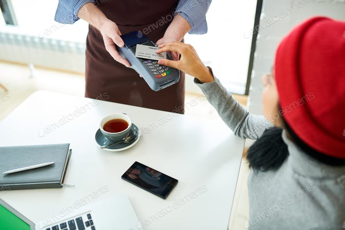 Young Woman Paying via NFC in Cafe