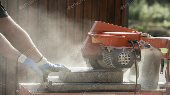 Side view of a man using an angle grinder