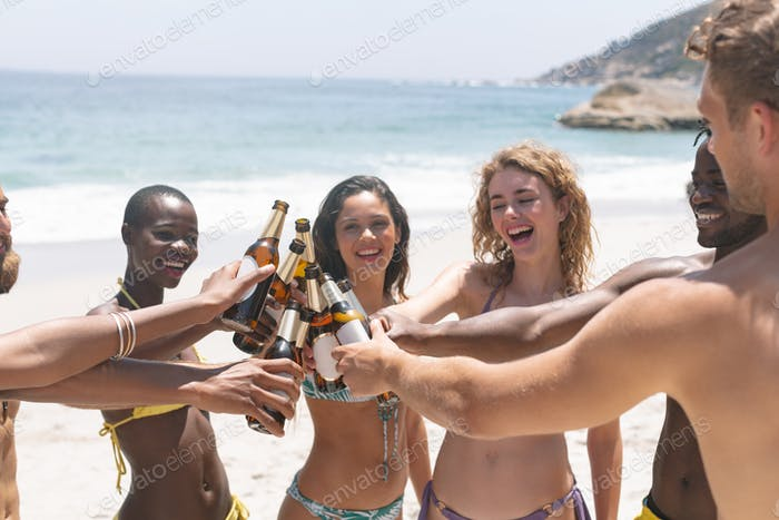 Happy diverse group of friends toasting with beer bottle at beach on a sunny day