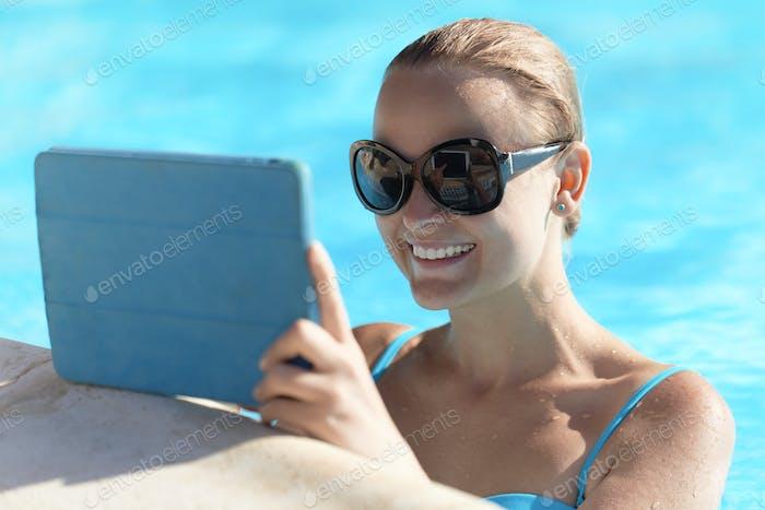 Junge Frau in einem Pool mit Tablet-Computer