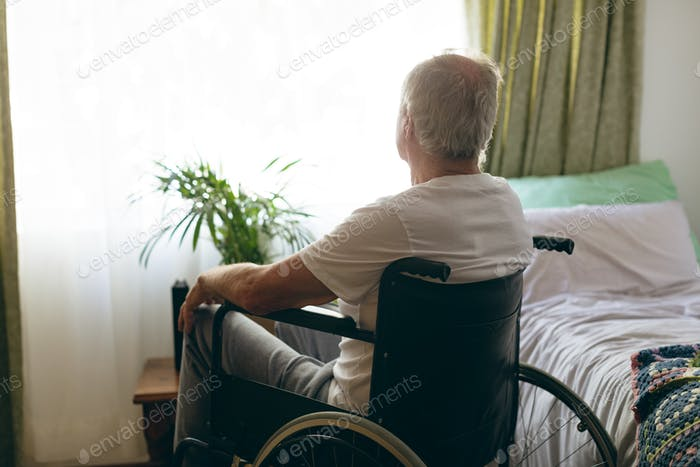 Senior male patient looking outside the window while sitting in wheelchair at retirement home