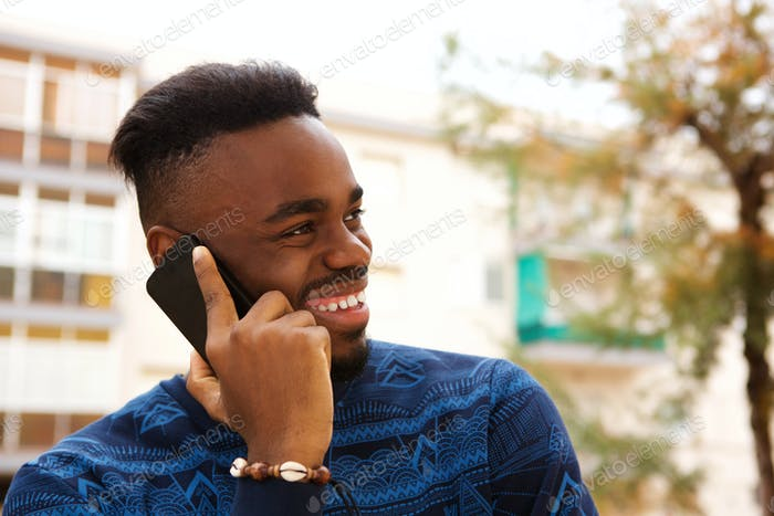 Happy african american man talking on mobile phone outside